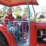 Bilde av Ane Terese, Maren Emilie og Silja som kjører traktor